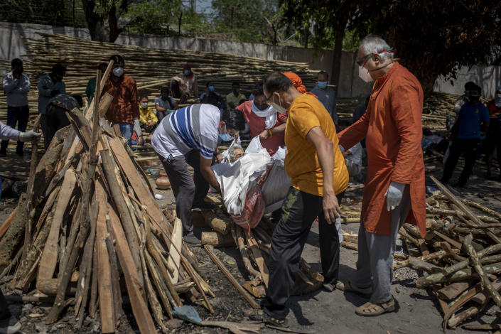 Family members put the body of their relative, who died of COVID-19 on the funeral pyre at a crematorium in New Delhi, India, Saturday, April 24, 2021. Delhi has been cremating so many bodies of coronavirus victims that authorities are getting requests to start cutting down trees in city parks, as a second record surge has brought India's tattered healthcare system to its knees. (AP Photo/Altaf Qadri)