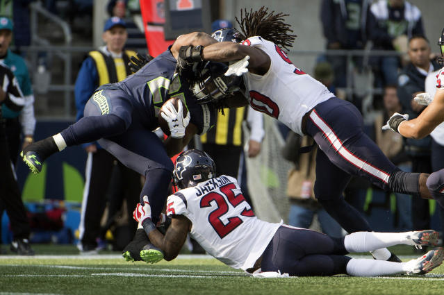 <p>Seattle Seahawks running back Eddie Lacy (27) is tackled by Houston Texans cornerback Kareem Jackson (25) and outside linebacker Jadeveon Clowney (90) during the first half at CenturyLink Field. Mandatory Credit: Troy Wayrynen-USA TODAY Sports </p>