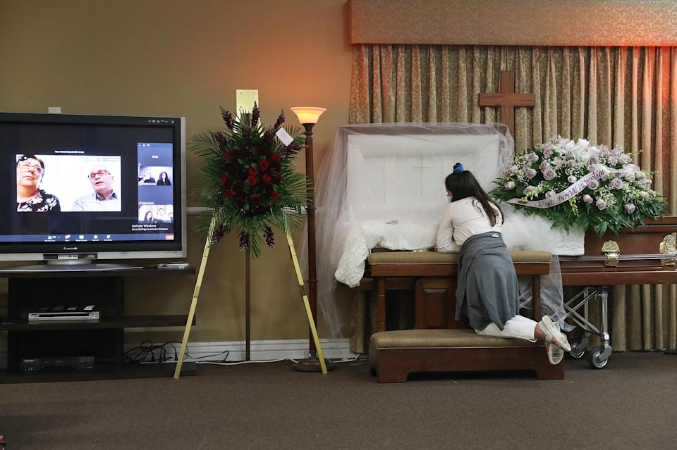 Asare Amaya, 10, mourns for her father, German Amaya, as family and friends are shown via a Zoom broadcast at the Maspons Funeral Home in Miami on Aug. 8, 2020. German Amaya, who died from COVID-19, had worked for 11 years at the Fontainebleau Miami Beach luxury hotel before he was furloughed in March. In late June, the family says, the hotel cut health care coverage for workers who had been laid off during the pandemic; in turn, the family lost his $10,000 death benefit.