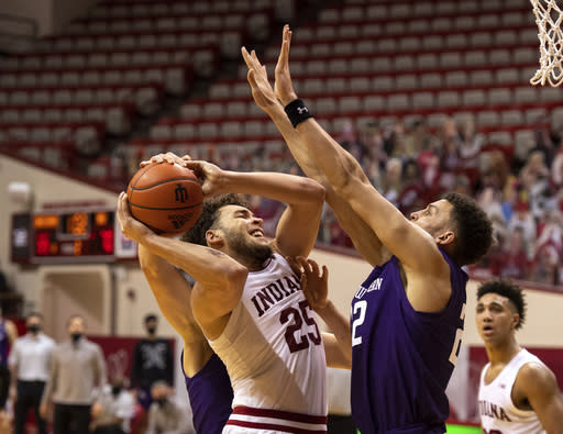 Indiana forward Race Thompson (25) is stopped en route to the basket by Northwestern forward Pete Nance (22) during the second half of an NCAA college basketball game, Wednesday, Dec. 23, 2020, in Bloomington, Ind. (AP Photo/Doug McSchooler)
