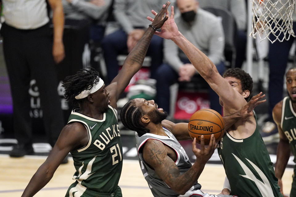 Los Angeles Clippers forward Kawhi Leonard, center, shoots as Milwaukee Bucks guard Jrue Holiday, left, and center Brook Lopez defend with their arms outstretched.