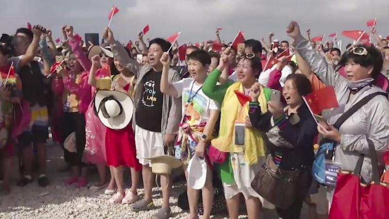 Chinese tourists hold flag-raising ceremony on disputed island in South China Sea