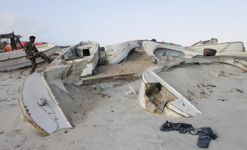 """FILE - In this Sunday, Sept. 23, 2012 file photo, a Somali government soldier walks next to some of the overturned pirate skiffs that litter the dunes on the shoreline near the once-bustling pirate den of Hobyo, Somalia. Frustrated by a string of failed hijacking attempts, Somali pirates have turned to a new business model: transporting weapons and providing """"security"""" for ships illegally plundering Somalia's fish stocks - the same scourge that launched the Horn of Africa's piracy era eight years ago. (AP Photo/Farah Abdi Warsameh, File)"""