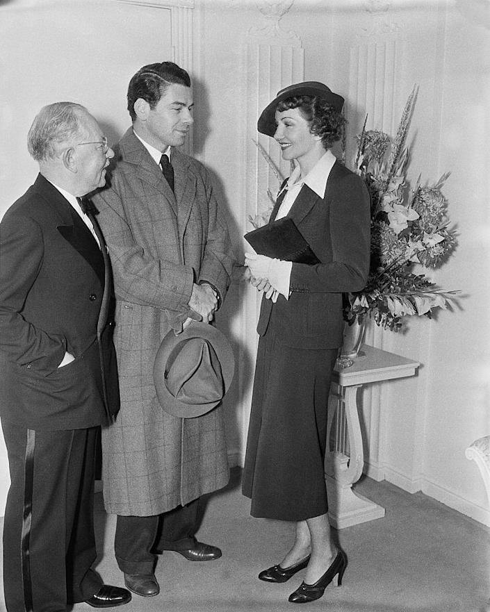 <p>Claudette Colbert chats with actor Paul Muni while wearing a midi skirt and matching jacket, accessorized with a fedora and pumps. </p>