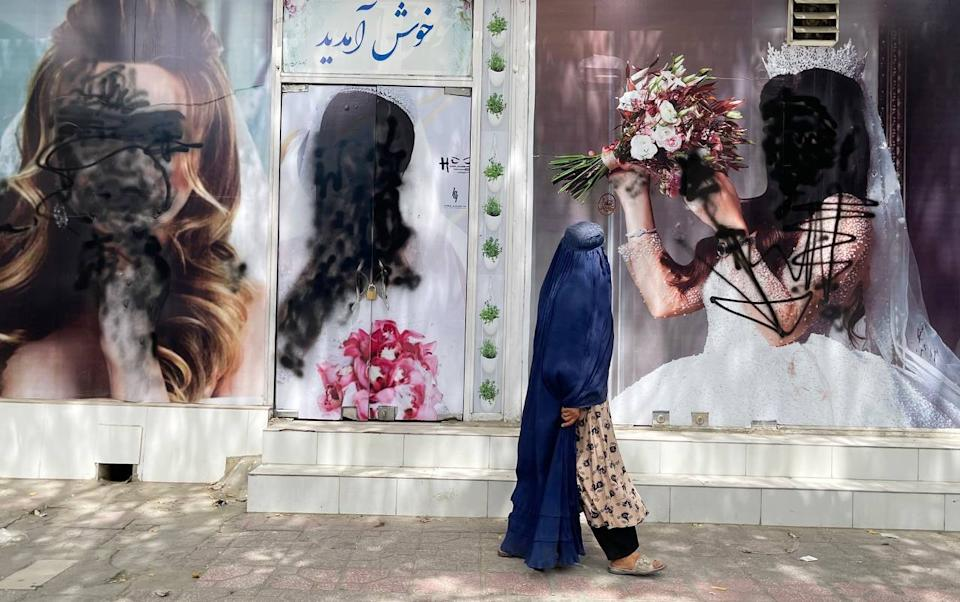 KABUL, AFGHANISTAN - AUGUST 20: Women posters on beauty salon windows remain vandalized in Kabul, Afghanistan on August 20, 2021. (Photo by Haroon Sabawoon/Anadolu Agency via Getty Images)