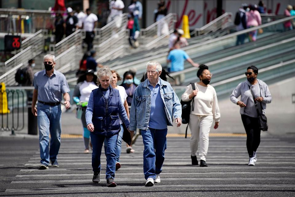 Masked and unmasked pedestrians walk across Las Vegas Boulevard, in Las Vegas. Elected officials in tourism-dependent Las Vegas worried Tuesday about public health and the economic effects of a spike in COVID-19 cases, particularly the highly contagious delta variant.