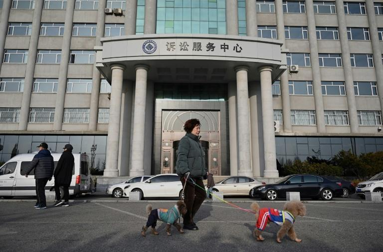 People walk in front of the Dandong Intermediate People's Court, where Canadian businessman Michael Spavor willgo on trial