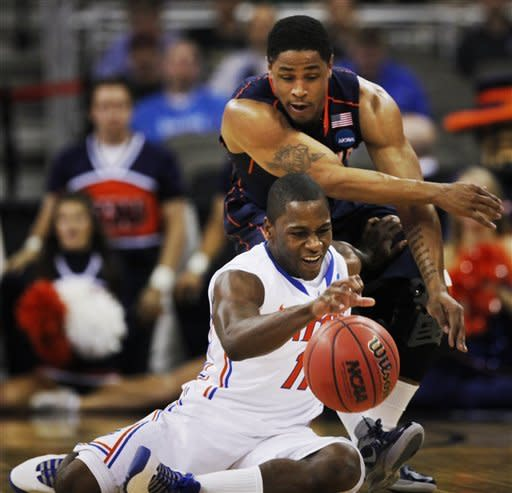 Florida guard Erving Walker (11) controls the ball while covered by Virginia guard Jontel Evans (1) during the first half of a second-round NCAA college basketball tournament game at CenturyLink Center in Omaha, Neb., Friday, March 16, 2012. (AP Photo/Nati Harnik)
