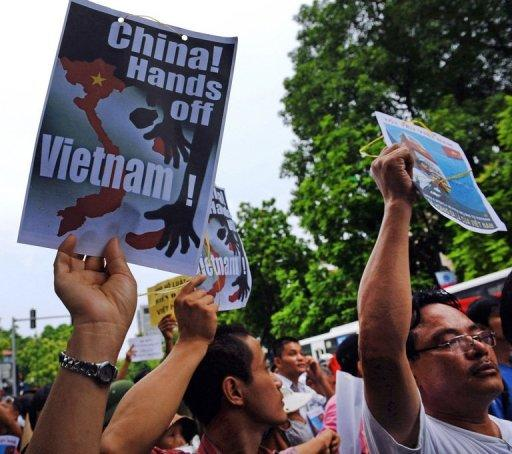 Vietnamese protesters hold up posters while shouting anti-China slogans in front of the Chinese embassy in Hanoi