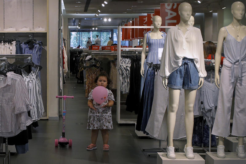 A child plays with a balloon at a clothing store having a promotion sale in Beijing, Monday, July 15, 2019. China's economic growth sank to its lowest level in at least 26 years in the quarter ending in June, adding to pressure on Chinese leaders as they fight a tariff war with Washington. (AP Photo/Andy Wong)