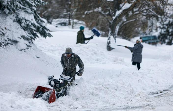 A trio digs out of the Green Mountain neighborhood on November 26, 2019 in Lakewood, Colorado (AFP Photo/Joe Mahoney)