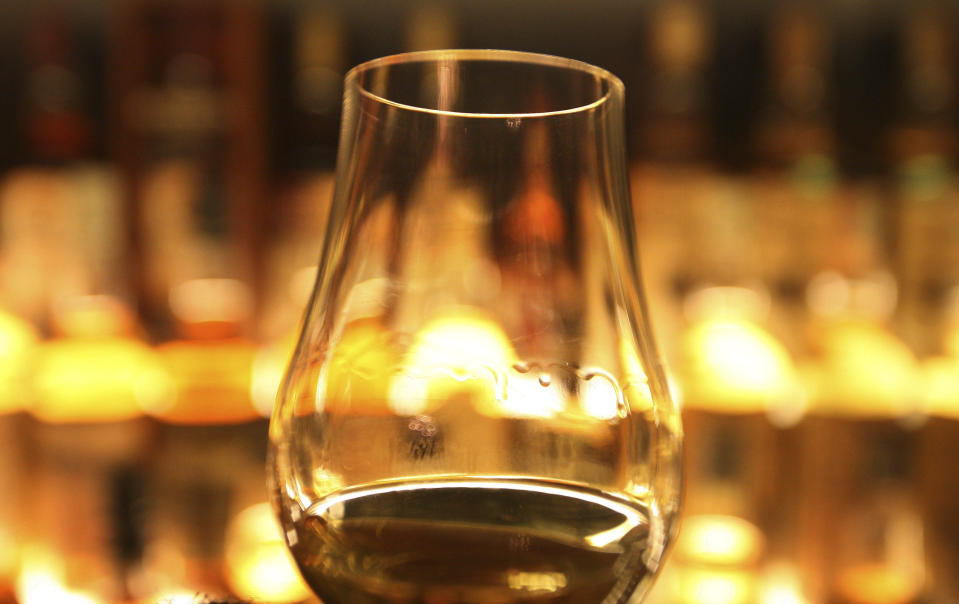 FILE- In this March 10, 2013 file photo, a glass of whisky is held up in front of the Diageo Claive Scotch Whisky collection in Edinburgh, Scotland. Scotland has called for Scotch to be defined in U.K. law so that the whisky industry can be protected after Brexit. (David Cheskin/PA via AP, file)