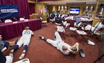 The Auburn baseball team watches the school's softball team play in the Women's College World Series in Oklahoma City during a weather delay in the baseball team's game against College of Charleston at the Tallahassee Regional of the NCAA college baseball tournament in Tallahassee, Fla., Sunday, May 31, 2015. (AP Photo/Mark Wallheiser)