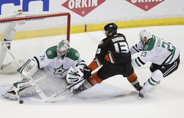 Dallas Stars' Kari Lehtonen, left, of Finland, stops a shot by Anaheim Ducks' Nick Bonino, center, as Stars' Kevin Connauton helps defend during the second period in Game 2 of a first-round NHL hockey Stanley Cup playoff series, Friday, April 18, 2014, in Anaheim, Calif. (AP Photo/Jae C. Hong)