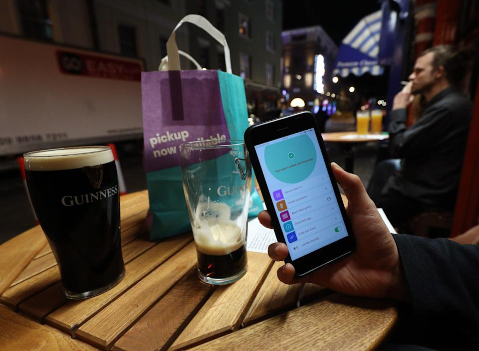 A person uses the NHS coronavirus contact tracing app outside The Coach and Horses pub in Soho, central London (PA)