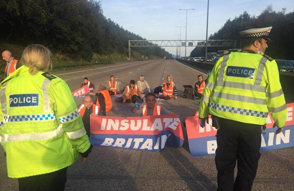 Handout photo issued by Insulate Britain of protesters occupying the clockwise and anti-clockwise lanes on the M25 in Surrey (PA Media)