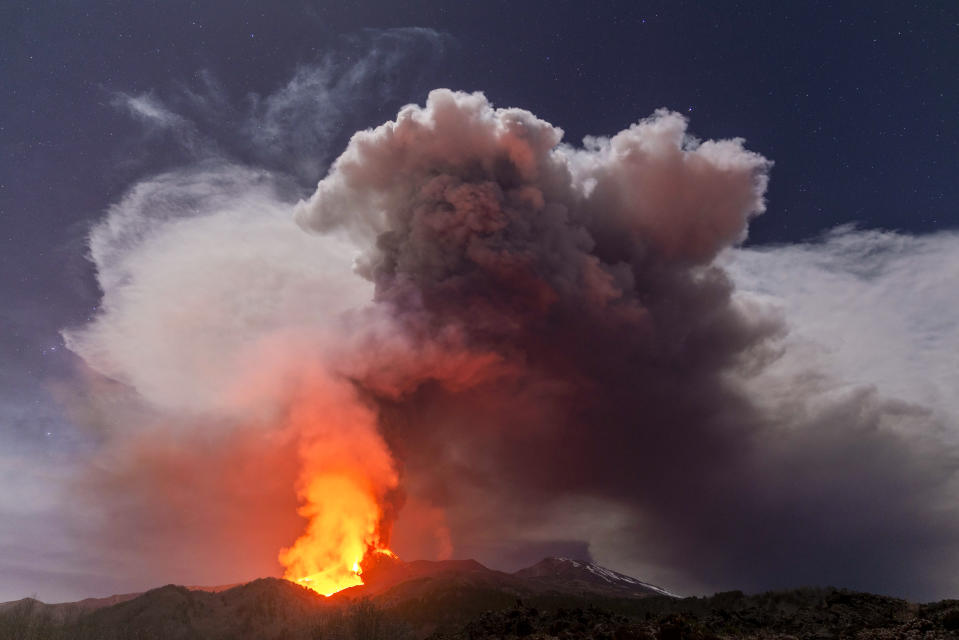 Glowing lava is seen from the north-east side of the Mt Etna volcano engulfed with ashes and smoke near Milo, Sicily, Wednesday night, Feb. 24, 2021. Europe's most active volcano has been steadily erupting since last week, belching smoke, ash, and fountains of red-hot lava. (AP Photo/Salvatore Allegra)