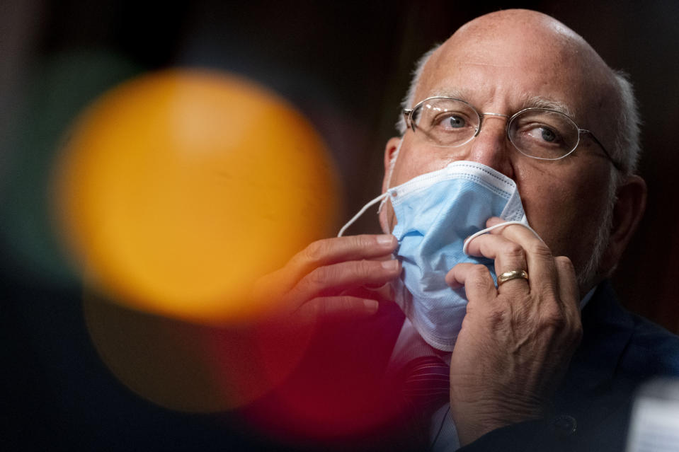 """FILE - In this Wednesday, Sept. 16, 2020, file photo, Centers for Disease Control and Prevention Director Dr. Robert Redfield puts his mask back on after speaking at a Senate Appropriations subcommittee hearing on a """"Review of Coronavirus Response Efforts,"""" on Capitol Hill, in Washington. The CDC has stirred confusion, by posting, and then taking down, an apparent change in its position on how easily the coronavirus can spread through the air. (AP Photo/Andrew Harnik, Pool, File)"""