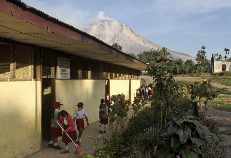 """Students prepare before the start of their class as Mount Sinabung is seen in the background, at an elementary school in Beganding, North Sumatra, Indonesia, Tuesday, Feb. 20, 2018. Volcanologists say Monday's eruption of the volcano that shot ash 5 kilometers (3 miles) high also """"annihilated"""" the mountain's summit. (AP Photo/Ahmad Putra)"""