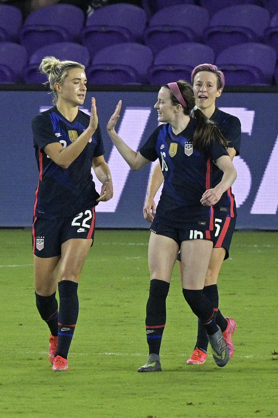 United States midfielder Kristie Mewis (22) is congratulated by midfielder Rose Lavelle (16) and forward Megan Rapinoe, right, after Mewis scored a goal during the first half of a SheBelieves Cup women's soccer match against Argentina, Wednesday, Feb. 24, 2021, in Orlando, Fla. (AP Photo/Phelan M. Ebenhack)