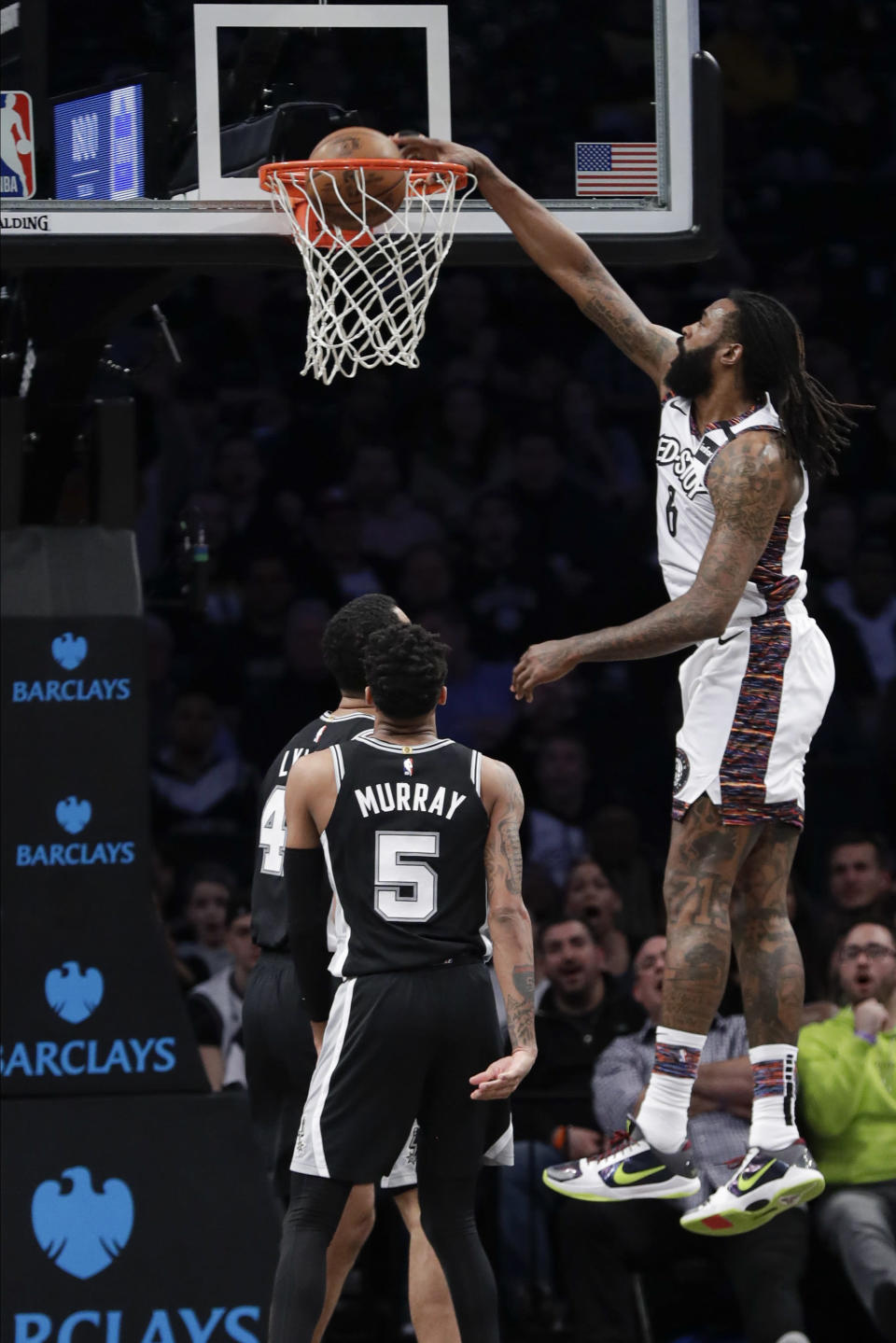Brooklyn Nets' DeAndre Jordan (6) dunks the ball in front of San Antonio Spurs' Derrick White (4) and Dejounte Murray (5) during the first half of an NBA basketball game Friday, March 6, 2020, in New York. (AP Photo/Frank Franklin II)