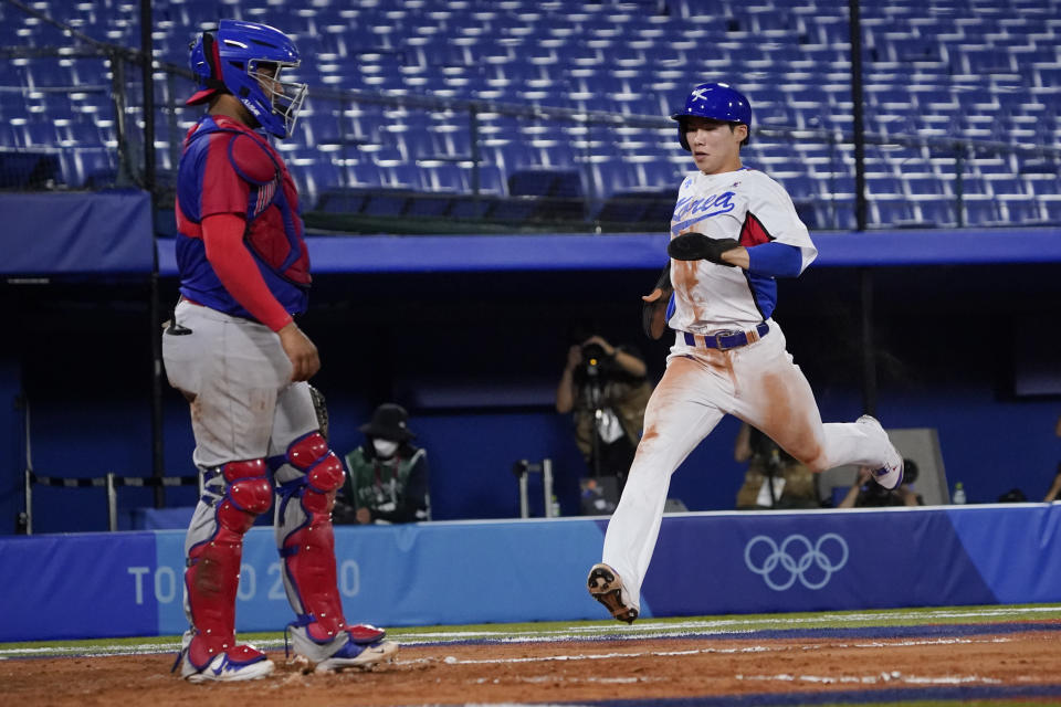 South Korea's Hyeseong Kim scores on a hit by Hae Min Park during the ninth inning of a baseball game against the Dominican Republic at the 2020 Summer Olympics, Sunday, Aug. 1, 2021, in Yokohama, Japan. (AP Photo/Sue Ogrocki)