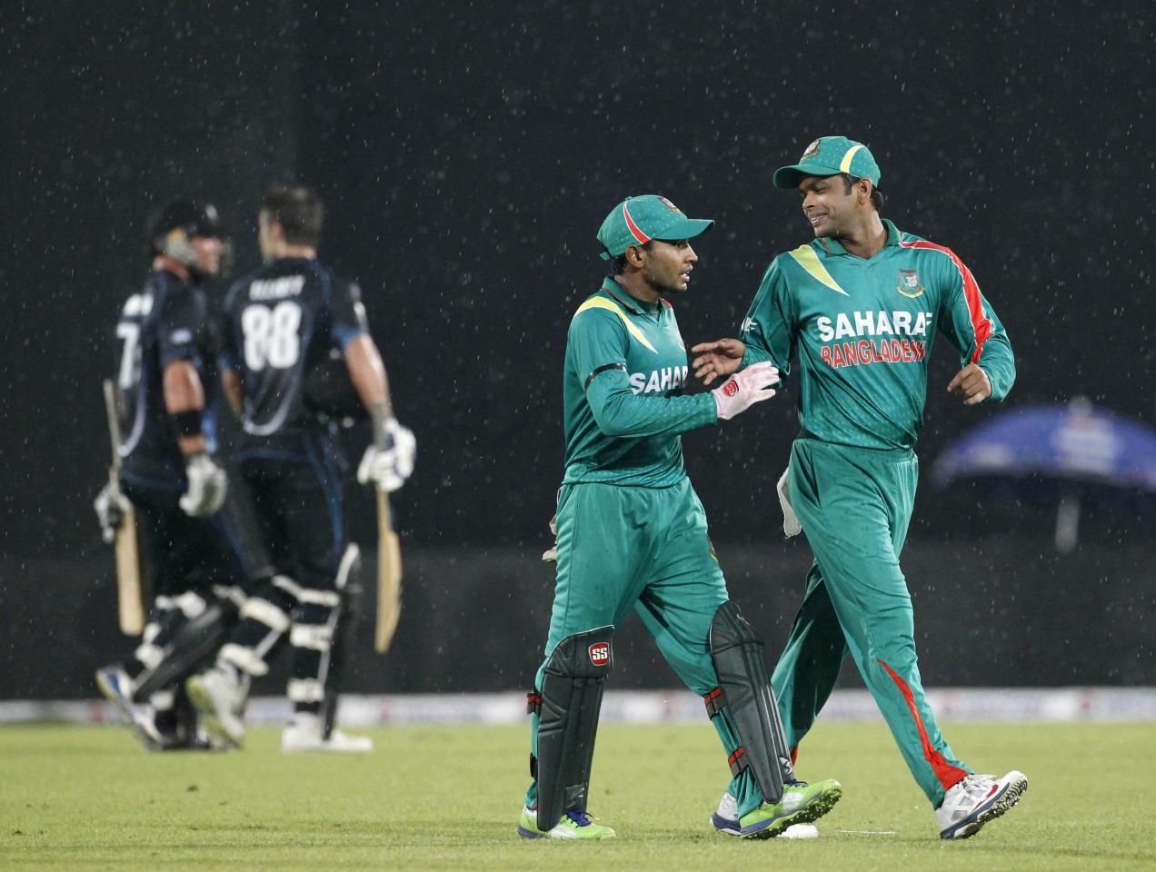 Bangladesh's captain Mushfiqur Rahim and Abdur Razzak (R) leave the field with New Zealand's Grant Elliott and Corey Anderson after rain inturupted the first one-day international (ODI) cricket match between New Zealand and Bangladesh in Dhaka October 29, 2013. REUTERS/Andrew Biraj (BANGLADESH - Tags: SPORT CRICKET ENVIRONMENT)