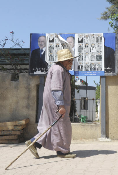 A man walks past electoral posters in Algiers, Wednesday, April 16, 2014. Algerians go to the polls Thursday to elect the president of their oil-rich country, a key U.S. ally in the fight against terror and a major natural gas provider to Europe. Six candidates are running for the presidency. President since 1999, Abdelaziz Bouteflika,77, is running for a 4th term despite being hit by a stroke last year that left him speaking and moving with difficulty. While he has not made a single campaign experience, he is expected to win with the full force of the state backing him. (AP Photo/Sidali Djarboub)