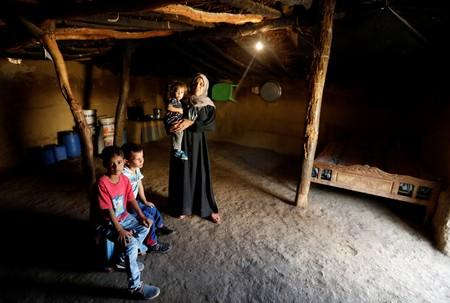 A blind mother and her children pose for a photo inside their home made of mud and stone and roofed with wicker and thatch in Oued al-Berber, Tunisia