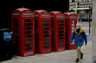 A man wearing a face mask walks past traditional red phone boxes during England's second coronavirus lockdown, in London, Friday, Nov. 20, 2020. Britain yesterday registered 501 daily COVID-19 deaths within 28 days of a positive test and is the fifth country in the world to record more than 50,000 coronavirus-related deaths. (AP Photo/Matt Dunham)