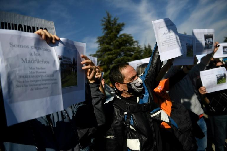 Funeral home employees hold signs calling for better conditions during a protest in Madrid on November 1, 2020.