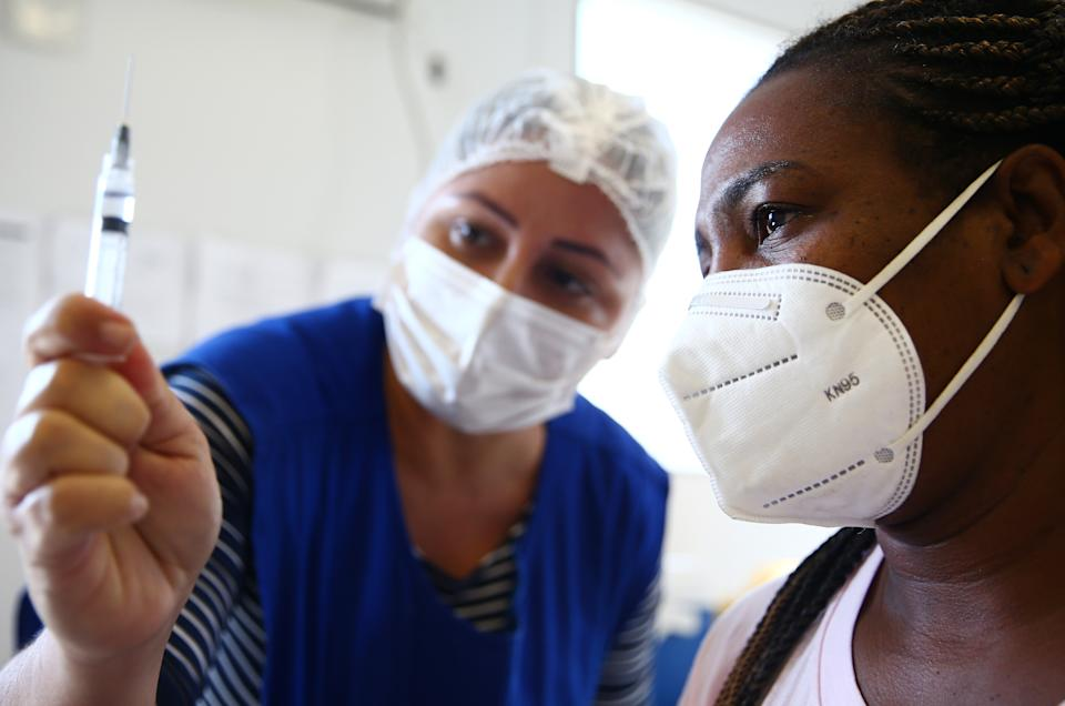 RIO DE JANEIRO, BRAZIL - MAY 26: Public health nurse Ana Maria Basilio prepares to administer a COVID-19 vaccination dose to Roberta Cristina da Cruz at a health post in the Manguinhos favela community on May 26, 2021 in Rio de Janeiro, Brazil. COVID-19 has now killed more than 1 million people in Latin America and the Caribbean, with nearly half of those killed in Brazil. Only three percent of the population of Latin America have been fully vaccinated against COVID-19. Health experts are warning that Brazil should brace for a new surge of COVID-19 amid a slow vaccine rollout and relaxed restrictions. 450,000 people have been killed in Brazil by COVID-19, second only to the U.S.  (Photo by Mario Tama/Getty Images)