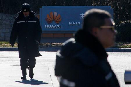 Security officers guard the gate to the compound of the Huawei office in Beijing, December 6, 2018. REUTERS/Thomas Peter