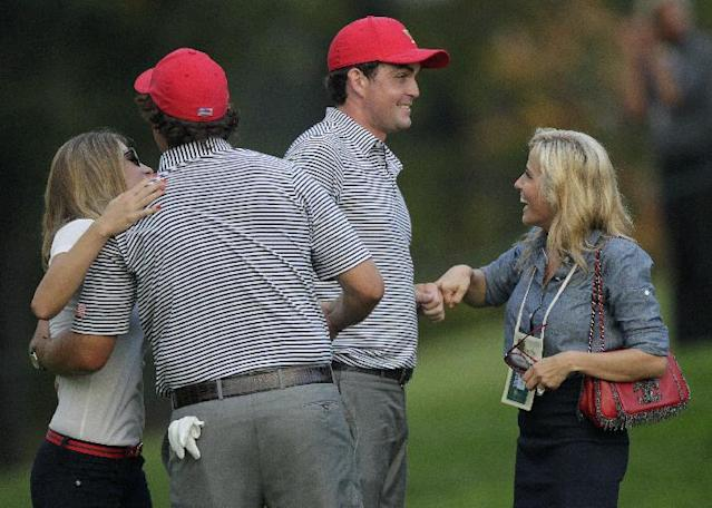 United States' Keegan Bradley, second from right, and Phil Mickelson, second from left, are congratulated by Bradley's girlfriend Jillian Stacey, left, and Mickelson's wife Amy after winning their foursome match 4 and 3 against the International's Jason Day and Graham DeLaet at the Presidents Cup golf tournament at Muirfield Village Golf Club Friday, Oct. 4, 2013, in Dublin, Ohio. (AP Photo/Jay LaPrete)