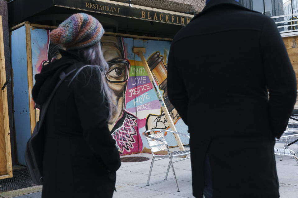 People walk past a mural of Supreme Court Justice Ruth Bader Ginsburg that was painted on a boarded up restaurant along I Street NW, Friday, Oct. 30, 2020, in downtown Washington near the White House. This restaurant has been boarded since protests this summer. (AP Photo/Jacquelyn Martin)