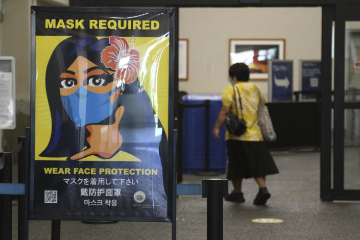 FILE - In this Oct. 2, 2020 file photo, a woman walks into the international airport in Honolulu amid a quarantine rule that effectively shut down the tourism industry in the state. The small, tight-knit community of about 72,000 people on the neighboring island of Kauai spent the first seven months of the pandemic mostly COVID-free. Then in October, statewide travel restrictions eased and the island, which had only 61 known cases of coronavirus from March through September, went from zero cases in October to at least 84 new infections in just seven weeks. (AP Photo/Caleb Jones, File)