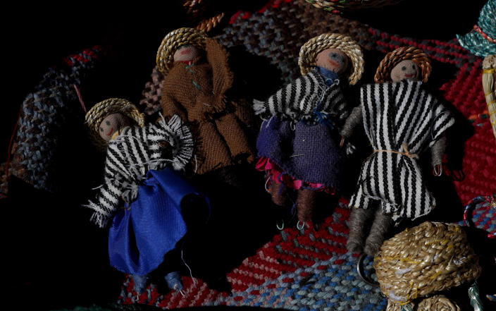 """Handmade dolls depicting an Uru family lay on a woven textile in the home of Evarista Flores, in the Urus del Lago Poopo indigenous community, in Punaca, Bolivia, Monday, May 24, 2021. For many generations, the Uru — """"people of the water"""" — would build a sort of family island of reeds when they married and would survive on what they could harvest from the broad, shallow lake in the highlands of southwestern Bolivia. (AP Photo/Juan Karita)"""