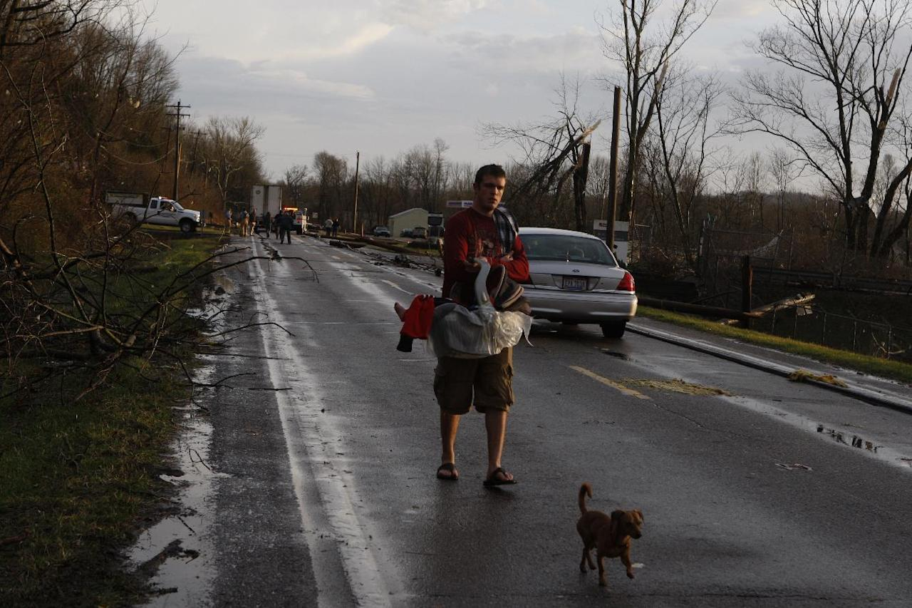 "Bill Lloyd carries his nine months old baby Mason down U.S. 52 outside Moscow after an apparent tornado moved through Moscow, Ohio Friday March 2, 2012. He said his house was ""gone"". (AP Photo/The Enquirer, Gary Landers)"