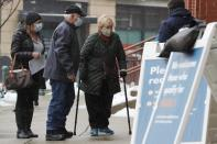 People arrive at a COVID-19 vaccination site at Fenway Park, Tuesday, Feb. 2, 2021, in Boston. (AP Photo/Michael Dwyer)