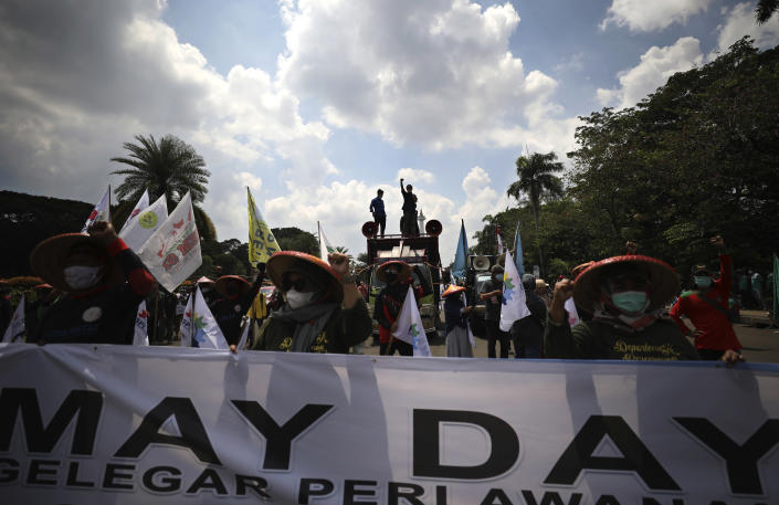 Indonesian workers shout slogan during a May Day rally in Jakarta, Indonesia, Saturday, May 1, 2021. Workers in Indonesia marked international labor day on Saturday curtailed by strict limits on public gatherings to express anger at a new law they say could harm labor rights and welfare. (AP Photo/Dita Alangkara)