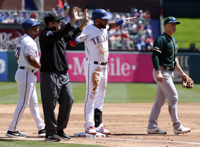 Texas Rangers' Elvis Andrus stands on third celebrating his run-scoring triple as base coach Tony Beasley, umpire Jansen Visconti and Oakland Athletics' Matt Chapman stand by in the first inning of a baseball game in Arlington, Texas, Sunday, April 14, 2019. The hit scored Delino DeShields. (AP Photo/Tony Gutierrez)