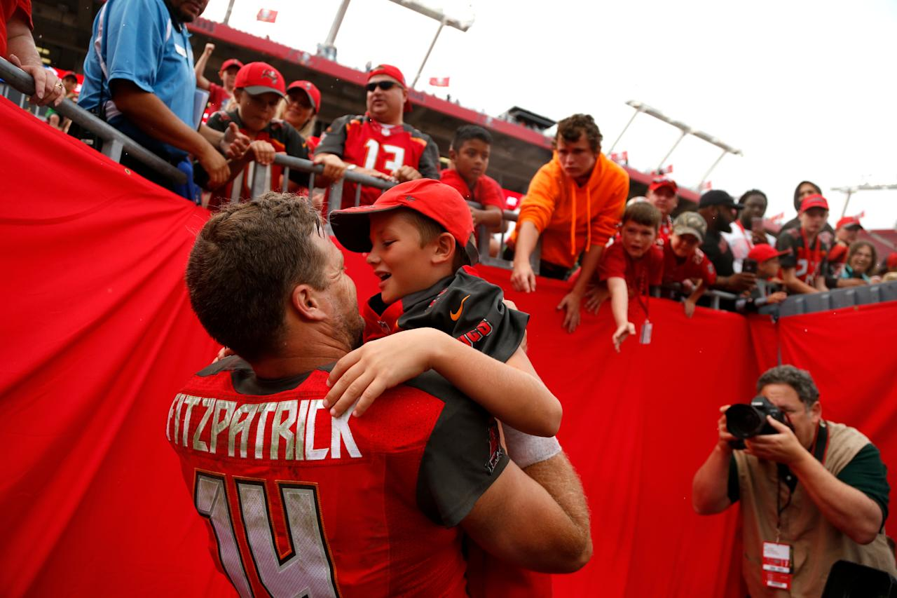 <p>Quarterback Ryan Fitzpatrick #14 of the Tampa Bay Buccaneers pulls on of his children out of the stands following the Buccaneers' 15-10 win over the New York Jets at an NFL football game on November 12, 2017 at Raymond James Stadium in Tampa, Florida. (Photo by Brian Blanco/Getty Images) </p>