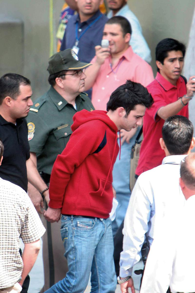 Diego Santoy, center, is escorted by police in Monterrey, Mexico, Tuesday, March 7, 2006. Santoy, 21, allegedly stabbed his ex-girlfriend, Erika Pena, 18, strangled her 3-year-old sister, and stabbed to death her 7-year-old brother, in an attack that shocked city residents. (AP Photo/Juan Manuel Villasenor)