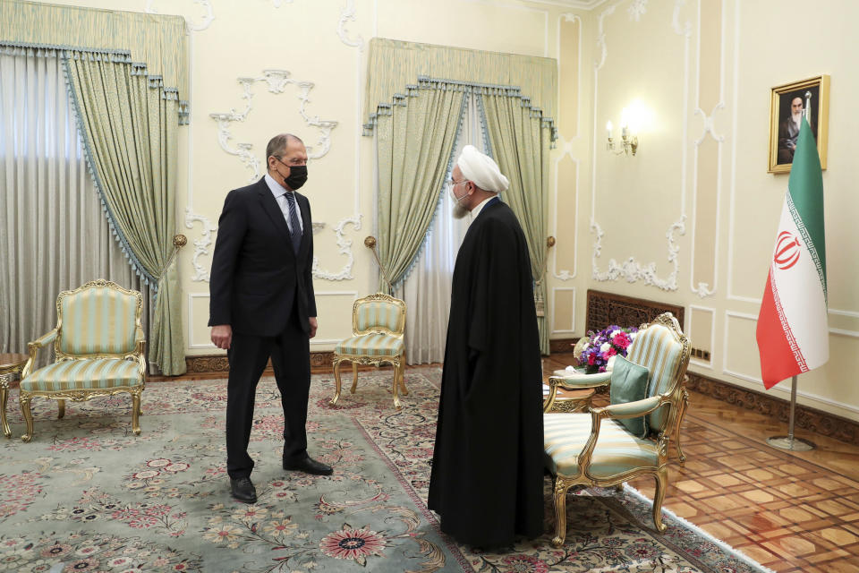 In this photo released by the official website of the office of the Iranian Presidency, Iranian President Hassan Rouhani, right, welcomes Russian Foreign Minister Sergey Lavrov, for their meeting in Tehran, Iran, Tuesday, April 13, 2021. (Iranian Presidency Office via AP)