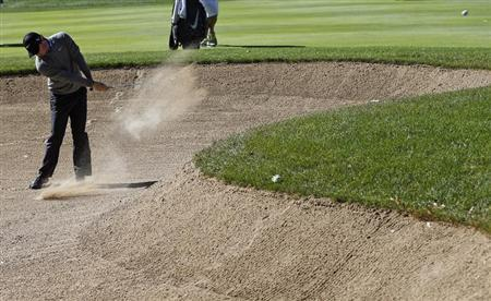 McIlroy of Northern Ireland hits out of the sand trap the first hole during the second round of the BMW Championship golf tournament at the Conway Farms Golf Club in Lake Forest