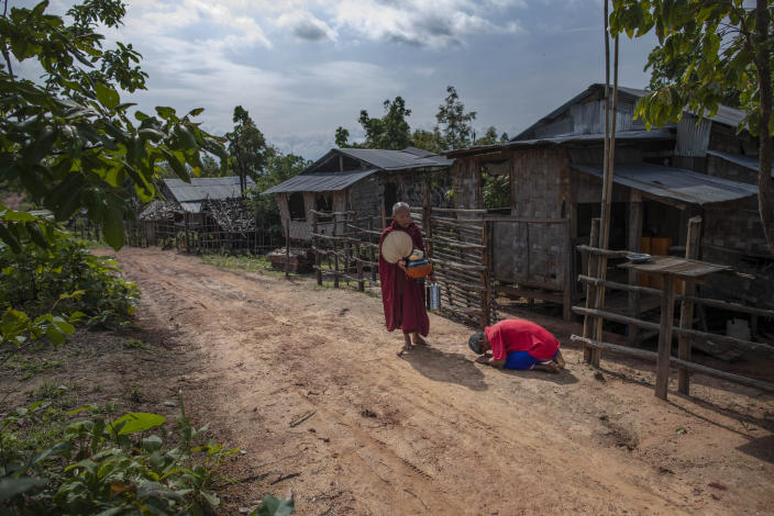 """Zin Ko Ko Htwe, who was trafficked twice, bows after offering alms to a Buddhist monk outside his mother's house in Myawaddy, Myanmar, Friday, June 14, 2019. Ko Htwe said after escaping from a fishing boat in 2008, he was sold onto a palm oil plantation run by a police officer in Malaysia. When Americans and Europeans see palm oil is listed as an ingredient in their snacks, they should know """"it's the same as consuming our sweat and blood,"""" he says. (AP Photo/Gemunu Amarasinghe)"""