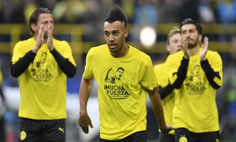 Pierre-Emerick Aubameyang and other Borussia Dortmund players wear a T-shirt reading 'Be strong, we are with you' in support of their team-mate Marc Bartra, who was injured in the bomb attacks.
