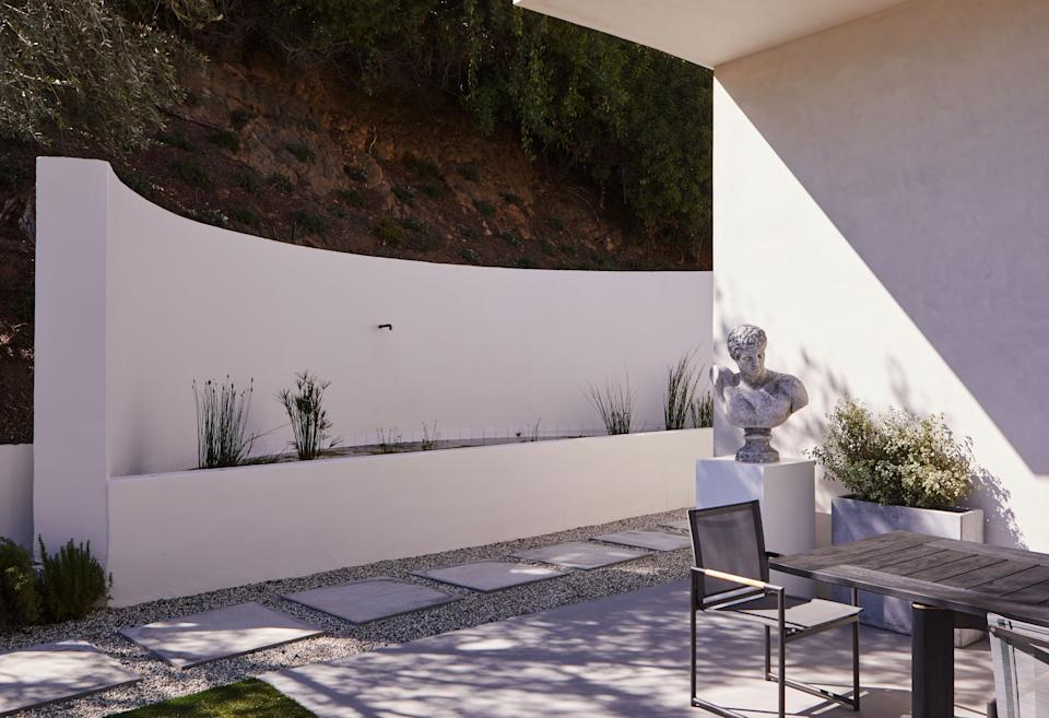 In this exterior area, adorned with a cast concrete sculpture of a man placed on a custom white pedestal, the Sonoma forge rustic nickel spout is from EuroConcepts and the Ora dining table and chairs are from Harbour Outdoor.
