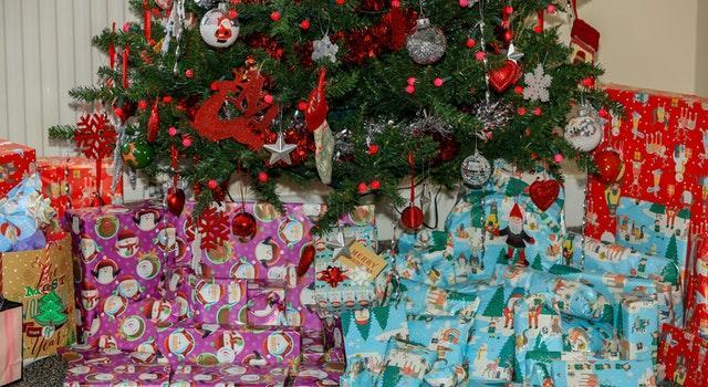 A pile of neatly wrapped Christmas presents beneath a Christmas tree (Peter Byrne/PA)