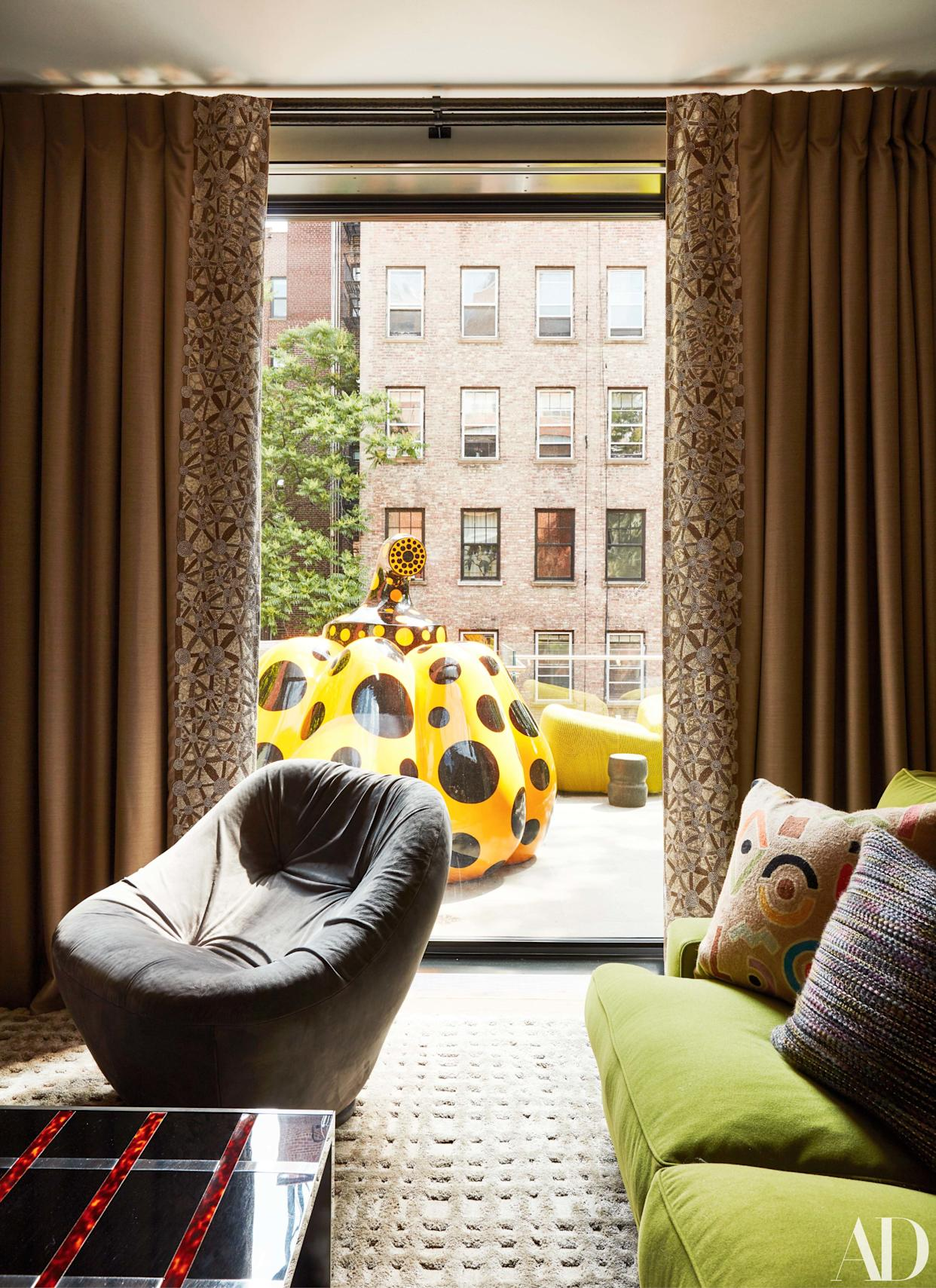 """<div class=""""caption""""> A pumpkin sculpture by Yayoi Kusama sits on a terrace outside the family room. </div>"""